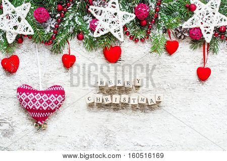 Merry Christmas. Christmas greeting card with fir tree decorations knitted and velvet hearts on rustic wooden background. top view