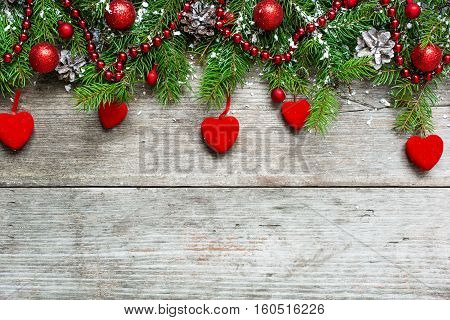 Christmas background with decorations velvet hearts and fir tree on wooden board with copy space. top view