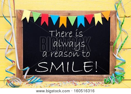 Blackboard With English Quote There Is Always A Reason To Smile. Party Decoration Like Streamer And Confetti. Yellow Wooden Background. Greeting Card For Celebrations