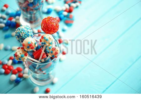 Glass with colorful small candies on table