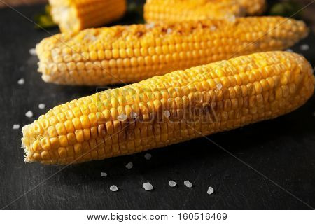 Tasty grilled corncobs with salt on dark background, close up view