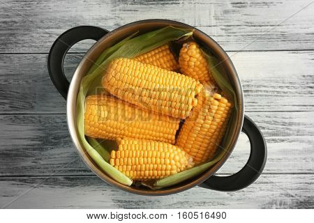 Tasty boiled corncobs in saucepan on wooden table