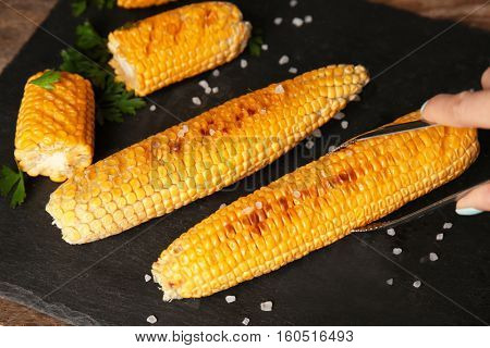 Female hand taking tasty grilled corncob from slate plate by using tongs, close up view
