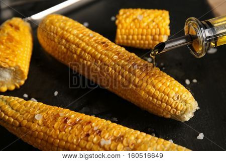 Tasty grilled corncobs with salt and oil on dark background, close up view