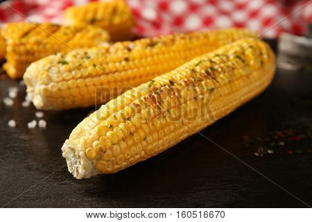 Tasty grilled corncobs with salt and herbs on dark background, close up view