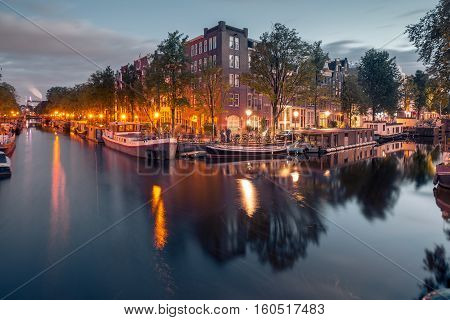 Amsterdam canals and typical houses, boats and bicycles during evening twilight blue hour, Holland, Netherlands.