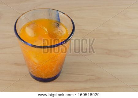 Orange soda pop with ice cubes in glass on wooden table