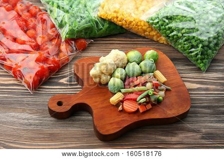 Frozen vegetables on wooden board