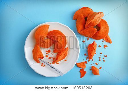 Plate with fortune cookies  on color background