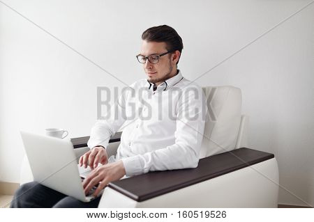 Young Man in Glasses checks mail sitting chair While Using Laptop. White Background