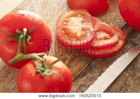 Freshly washed ripe red tomatoes with water droplets whole on the vine and sliced on a wooden cutting board with a kitchen knife