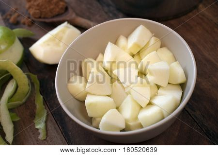 Preparing the ingredients for apple sauce with diced fresh green cooking apples in a bowl with ground aromatic cinnamon spice for flavoring