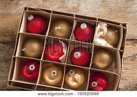 Cardboard carton of red and gold Christmas balls ready to decorate the house for the festive holiday season viewed from above on a rustic wood table
