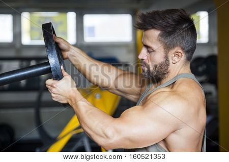 An image of a male bodybuilder preparing the weight