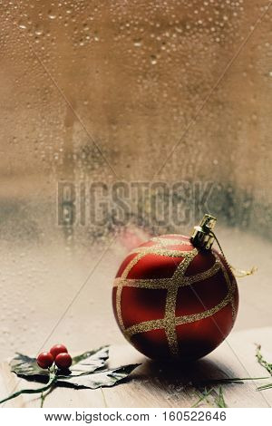 a twig of holly and a red and golden christmas ball on a rustic wooden table in front of a window splattered with raindrops