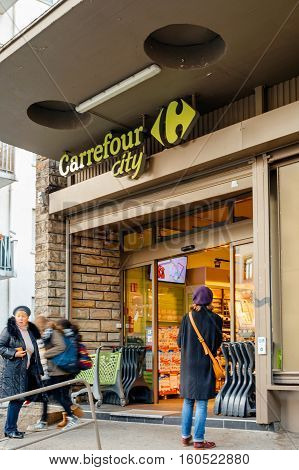 STRASBOURG FRANCE - DEC 1 2016: People entering Carrefour supermarket at the evening to buy diverse food and non-food products. Carrefour is the largest chain of stores in France