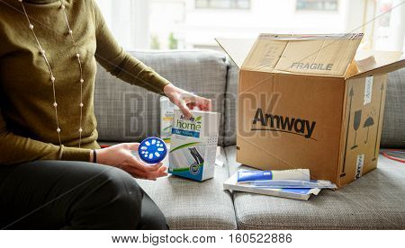 PARIS FRANCE - OCT 20 2015: Woman unpacking unboxing cardboard carton box with protective foam pads inside after buying ordering online via internet Multi-level marketing products from Amway