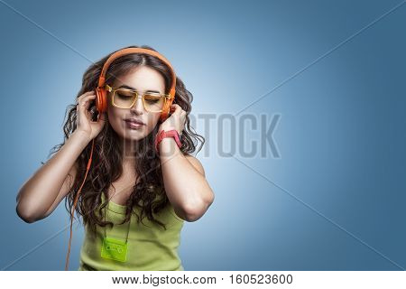 Girl In Headphones And Glasses Looking Down And Listening Music