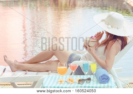 Young female on vacation chilling with cocktail beside a swimming pool