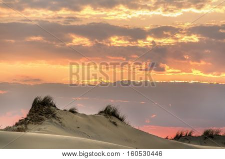 Dunes at North Carolina's Jockey's Ridge Stae Park are topped by a colorful sunset sky.