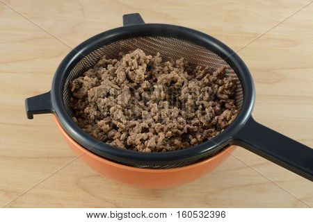 Draining fat and grease from cooked hamburger meat in strainer in bowl for spaghetti sauce