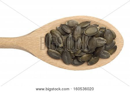 Pumpkin seeds in a wooden spoon isolated on white background