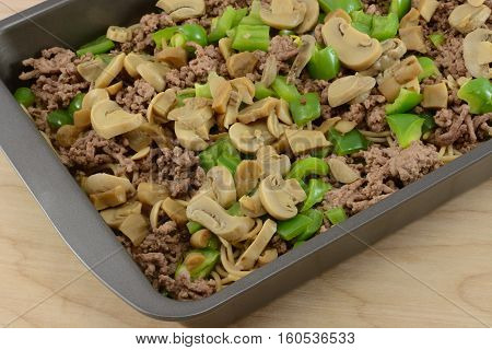 Close up spaghetti casserole layers of canned mushrooms, chopped green bell peppers, cooked hamburger meat and whole wheat rotini pasta in pan