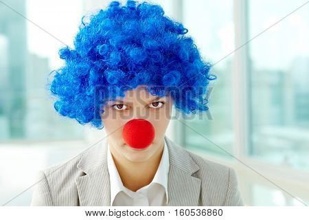 Portrait of a businesswoman in clown wig and nose