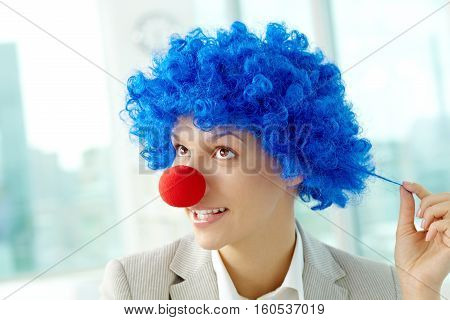 Portrait of a dreaming businesswoman in clown wig and nose