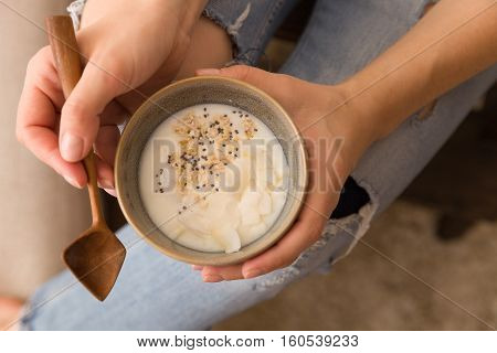 Closeup of woman's hands holding cup with organic yogurt with coconut and chia seeds. Homemade vanilla yogurt in girl's hands. Breakfast, snack. Healthy eating and lifestyle concept