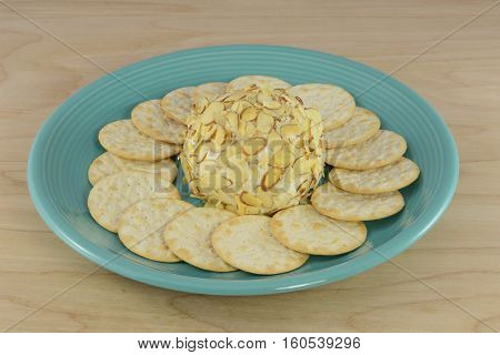 White chocolate amaretto cheeseball with almond topping with table water crackers on blue plate