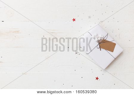 Top view on nice Christmas gift wrapped in white gift paper, Christmas tree decorations on white wooden background with sparkling stars. New Year, holidays and celebration concept