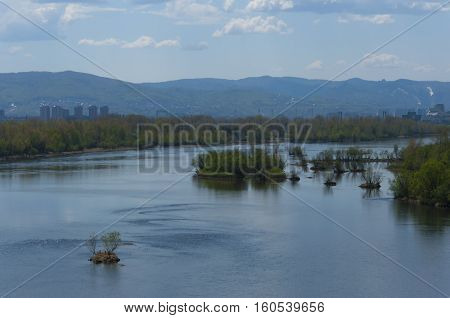 River landscape islands in the middle of the river against the background of the blue sky with clouds