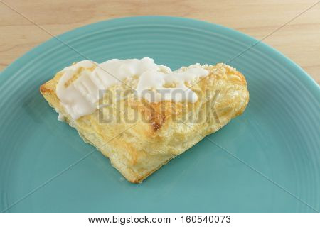 Apple turnover with frosting on blue plate