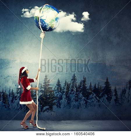 Elegant Santa woman pulling Earth planet on rope, Elements of this image furnished by NASA