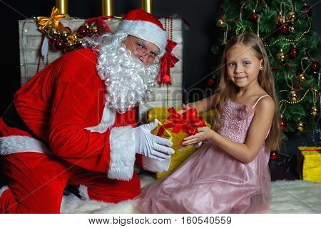 Santa Claus and a girl in a dress. Christmas Scenes. Santa gives a gift in a box for a cute little girl