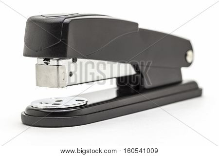 Stationery black office stapler close up on a white background.