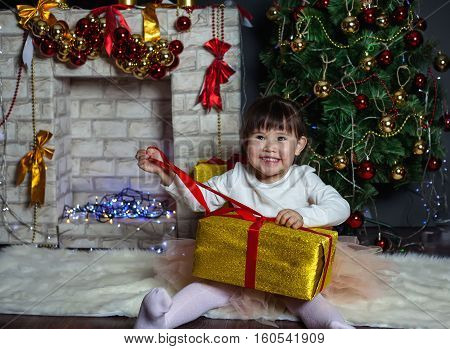 Little girl unleashes the gift. Christmas Scenes. Posing smiling