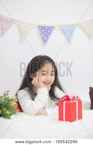 Happy Asian girl looking a present to guess whats inside