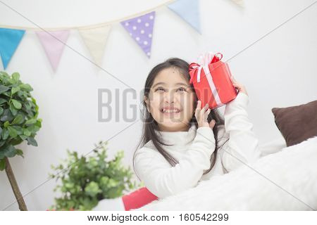 Happy Asian girl shaking a present to guess whats inside