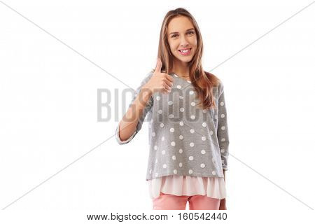 Mid shot of pleased youth giving thumb up gesture indicating approval and respectively isolated over white background. Fist held with the thumb extended upward