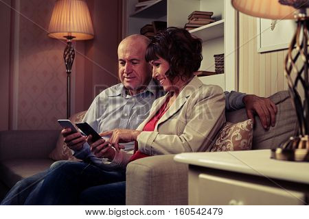 A mid shot of a pair communicating with one another, smiling and pointing at something funny on their mobiles. Elderly man and woman sitting in a room with an excellent modern interior