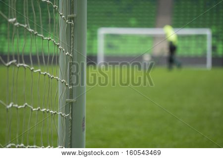 Soccer or football goal through the net. Games in Brazil. Man mows the grass