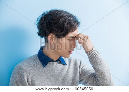 man student feel eye discomfort with isolated blue background asian