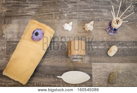 On a surface of wood are a beige towel with a purple carrot a tea light holder shells stones a candle in the shape of a leaf and a container with fragrance oil