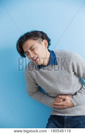 man feel stomach ache with isolated blue background asian