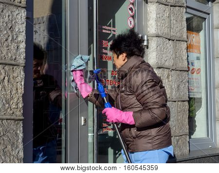 Yalta, Russia - November 13, 2015: Elderly woman washes the glass doors of the store from the street