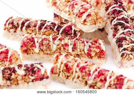 Cereal bars with different berries and seeds on white background.