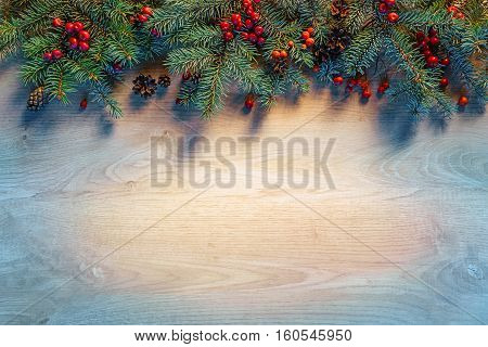 Christmas fir tree on wooden table in dark. Merry Christmas and Happy New Year!! Top view.