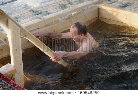 Man Bathes Into Cold Water Of Ice-hole On Epiphany Day. Russia